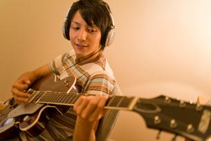 ヘッドホンをかけてギターの練習をする男性の写真素材 [FYI02966127]