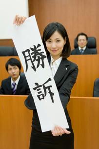 勝訴の紙を持った若い女性の写真素材 [FYI02966138]