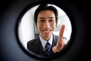 覗き窓越しの笑顔の営業マンの写真素材 [FYI02966142]