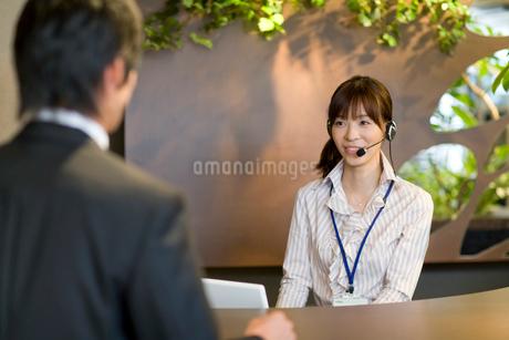 受付で対応をする女性の写真素材 [FYI02966146]
