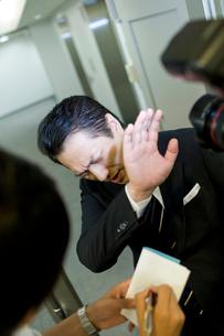 写真を撮られて嫌がる男性の写真素材 [FYI02966151]