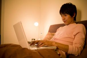 ベッドでパソコンのキーボードを打つ男性の写真素材 [FYI02966170]
