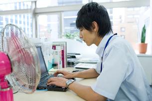 扇風機のあるデスクでパソコンをする男性の写真素材 [FYI02966198]