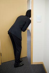 扉の中を覗くビジネスマンの後姿の写真素材 [FYI02966200]