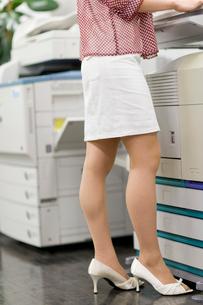 コピー機の前に立つ女性の下半身の写真素材 [FYI02966202]