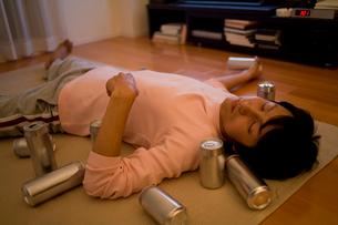 缶に囲まれて床で眠る男性の写真素材 [FYI02966225]