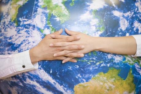 地球を握る男女の手元の写真素材 [FYI02966227]