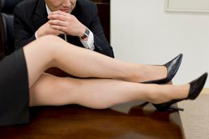 机の上に乗った女性の足を見る男性の写真素材 [FYI02966228]