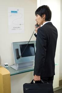 会社の受付で受話器を持った男性の写真素材 [FYI02966232]