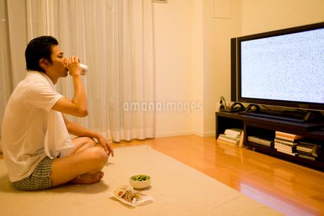 缶ビールを飲みながらテレビを見る男性の写真素材 [FYI02966236]
