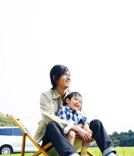 草原で椅子に座って寛ぐ父と息子の写真素材 [FYI02966244]