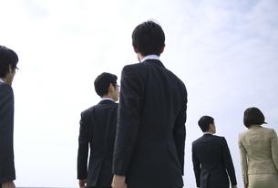 遠くを見ながら立つビジネス男女の後ろ姿の写真素材 [FYI02966257]
