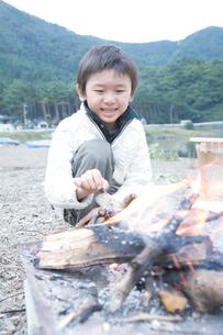 湖畔で焚火をおこす男の子の写真素材 [FYI02966258]