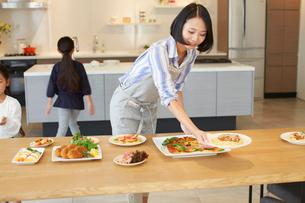 テーブルに食事を用意する親子の写真素材 [FYI02966263]