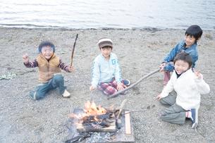 湖畔でおこした焚火を囲む4人の男の子の写真素材 [FYI02966266]
