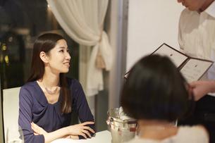 レストランで店員の話を聞く女性二人の写真素材 [FYI02966271]