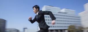 ビルを背景に走るビジネス男性の写真素材 [FYI02966277]