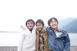 湖畔で肩を組んで笑う3人の男の子の写真素材 [FYI02966280]