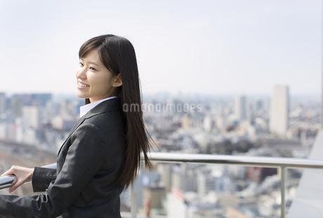 屋上で遠くを見ながら微笑むビジネス女性の写真素材 [FYI02966281]