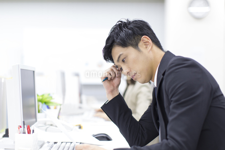 デスクで資料を見て考えるビジネス男性の写真素材 [FYI02966283]