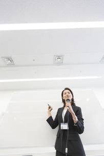 マイクを手に講義するビジネス女性の写真素材 [FYI02966290]