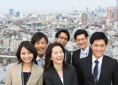 ビル群を背景に笑うビジネス男女の写真素材 [FYI02966293]