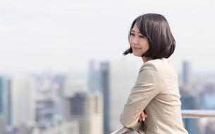 屋上でビル群を眺めるビジネス女性の写真素材 [FYI02966294]
