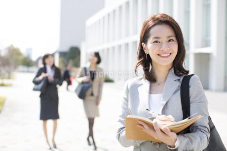手帳を手にカメラ目線のビジネス女性の写真素材 [FYI02966298]