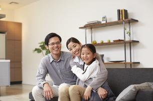 ソファーで笑顔の3人家族の写真素材 [FYI02966299]