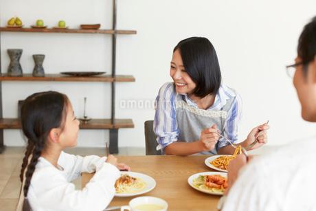 食事をしながら娘に微笑む奥さんの写真素材 [FYI02966302]