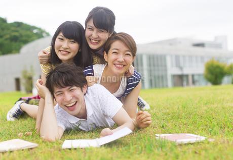 芝の上で重なって笑う学生たちのポートレートの写真素材 [FYI02966304]