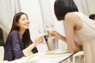 レストランでワインを手に笑い合う女性二人の写真素材 [FYI02966306]