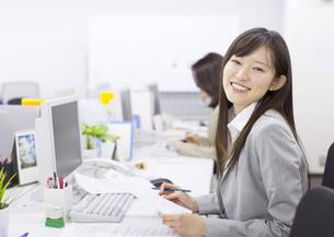 デスクで資料を手に微笑むビジネス女性の写真素材 [FYI02966311]