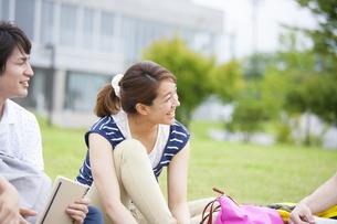 芝に座り談笑する学生の写真素材 [FYI02966317]