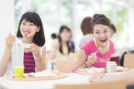学食で食べるポーズをする2人の女子学生の写真素材 [FYI02966323]