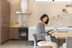 ダイニングテーブルで本を読みながら微笑む女性の写真素材 [FYI02966325]