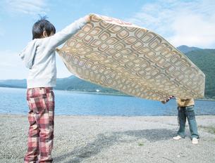 湖畔にシートを広げる2人の男の子の写真素材 [FYI02966326]