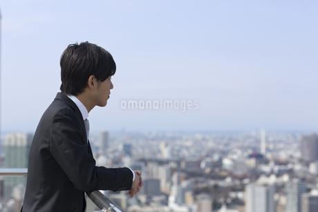 屋上でビル群を眺めるビジネス男性の写真素材 [FYI02966333]