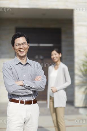 夫が手前で家の前に立つ夫婦の写真素材 [FYI02966339]