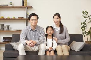 女の子を中心にソファーに座る3人家族の写真素材 [FYI02966341]