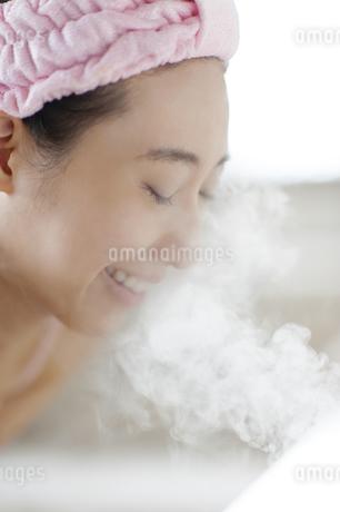 スチーマーで顔のケアをする女性の写真素材 [FYI02966342]