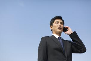 スマートフォンで話すビジネス男性の写真素材 [FYI02966347]