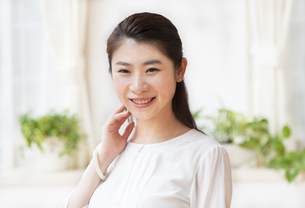 顔に手を添えて微笑む女性の写真素材 [FYI02966348]