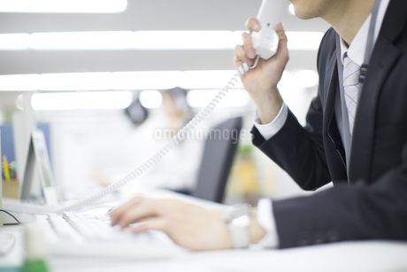 受話器を手にするビジネス男性の手の写真素材 [FYI02966349]