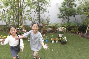 庭でシャボン玉を追いかける姉妹の写真素材 [FYI02966351]