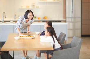 テーブルで笑い合う母と姉妹の写真素材 [FYI02966353]