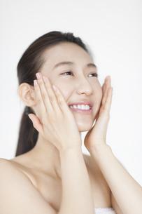 頬に両手を添えて微笑む女性の写真素材 [FYI02966354]