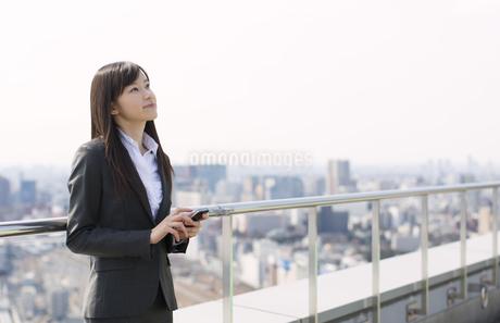 屋上でスマートフォンを手に上を見るビジネス女性の写真素材 [FYI02966362]