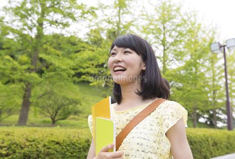 微笑みながら緑道を歩く女子学生の写真素材 [FYI02966363]