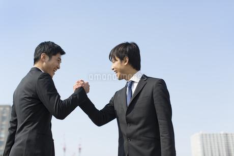笑顔で手を組むビジネス男性2人の写真素材 [FYI02966364]